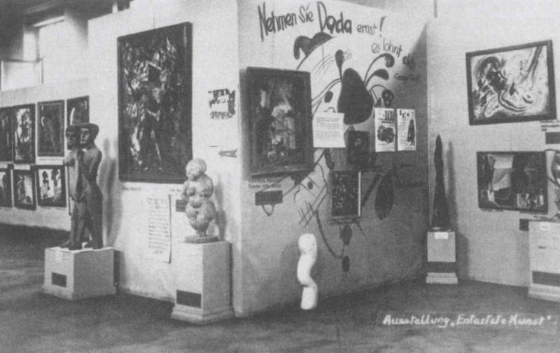 Vista de la exposición Arte degenerado, Múnich, 1937, sala 3, planta superior (conocida comola «pared dadá») con obras de George Grosz, Kurt Schwitters, Vasily Kandinsky (pintura mural), Paul Klee,Raoul Hausmann, Lyonel Feininger y esculturas de Ernst Ludwig Kirchner, Christoph Voll, Rudolph Haizmann,Oswald Herzog y Margarethe Moll